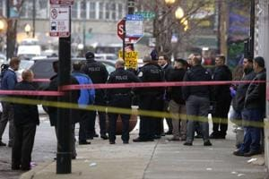 Chicago police officers investigate the scene where four people were shot and killed at a restaurant in the 2700 block of East 75th Street in Chicago, Illinois.
