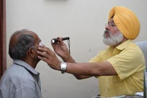 District programme manager Dr Shamsher Singh examining a patient at civil hospital in Jalandhar on Saturday.