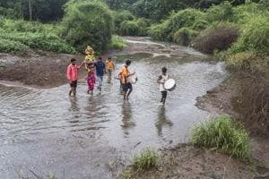 Members of a local adivasi clan cross Dahisar River with an idol of goddess Durga
