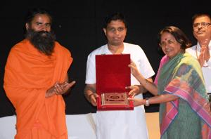 DRDO (Life Sciences) head Sashibala Singh presenting memento to Balkrishna as Ramdev looks on.