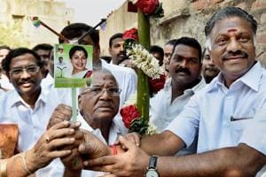 AIADMK leader and former Tamil Nadu chief minister O Panneerselvam presents the party symbol (electric pole) to the RK Nagar bypoll candidate E Madhusudhanan in Chennai on March 26, 2017.