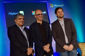 Microsoft CEO Satya Nadella (C) is flanked by EkStep founder Nandan Nilekani (L) and founder of FlipKart Binny Bansal (R) during an event bringing together digital industry leaders in Bangalore on February 20, 2017. / AFP PHOTO / -