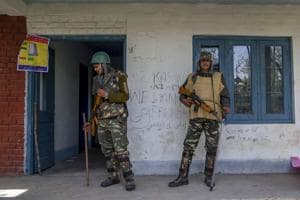 Soldiers stand guard near the entrance of a polling station with pro-freedom and anti election graffiti on the wall in Srinagar, April 13