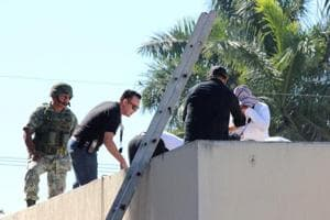 A soldier stands guard as forensic technicians work at a crime scene where the body of a man, who witnesses said was tossed from a plane, landed on a hospital roof in Culiacan, in Mexico