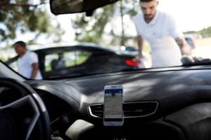 An Uber driver cleans his car as his cell phone shows the queue to pick up passengers departing Guarulhos International Airport.