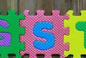 Colourful puzzle block letter with word GST on wood background.