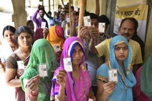 Voters stand in a queue at a polling station at Madanpur Khadar in New Delhi on Sunday.