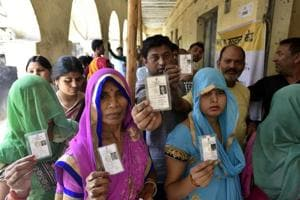 Voters stand in a queue at a polling station at the cast their votes at Madanpur khadar in New Delhi on Sunday.
