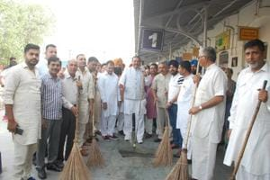 BJP state chief Vijay Sampla cleaning railway station with supporters in Phagwara on Sunday.