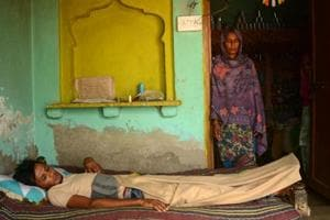 Azmat, who has suffered a spine injury, lying on a cot at his home in Jaisinghpur in Nur district of Haryana. His mother looks on.