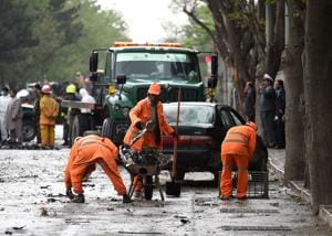 Afghan municipality workers clear the site of a suicide attack that targeted a foreign forces convoy near the US embassy in Kabul on May 3, 2017.
