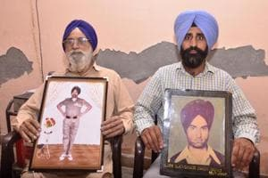 Ex-servicemen (left) Joginder Singh showing a picture during service and (right) Daljit Singh showing picture of his father Kashmir Singh who was martyr in Kargil, at Pandori Sidhwan village on Wednesday.
