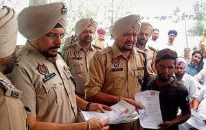 A villager handing over an affidavit, pledging to stay away from drugs, to SSP (rural) Surjit Singh at Khurshidpura village in Ludhiana on Saturday.
