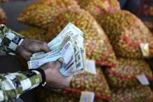 A trader counts rupees at wholesale vegetables market on the outskirts of Jammu on March 6.