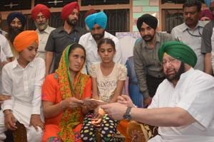 Chief minister Capt Amarinder Singh with the family of martyr Paramjit Singh at Vein Poin village in Tarn Taran on Sunday.