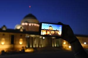 An  illuminated Rashtrapati Bhavan being captured on a mobile phone.