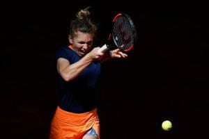 Simona Halep of Romania, the defending champion, returns to Roberta Vinci of Italy during their WTA Madrid Open match on Tuesday.