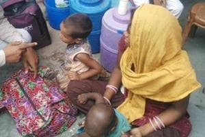 Rita, with her two children, talks to Naresh Paras in Agra on Saturday.