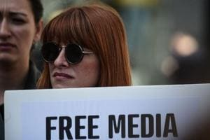 """A journalist holds a placard reading """"free media"""" during a demonstration for the World Press Freedom Day  in Istanbul, May 3.  In Turkey, the constitution has been changed by a wafer thin margin and Recep Erdogan is set to be remake his country in his image, while the jails fill with purged bureaucrats, soldiers, journalists and cartoonists."""