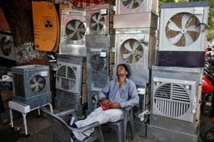 A man selling air coolers rests at a market on a hot summer day in Ahmedabad.