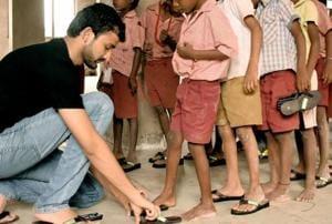 Shriyans Bhandari  distributing slippers to  underprivileged children .