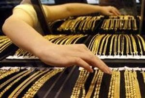 An employee arranges gold jewellery in the counter.