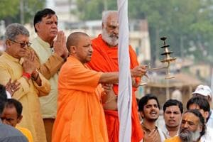 Uttar Pradesh chief minister Yogi Adityanath holds a traditional lamp as he performs prayers on the banks of river Sarayu in Ayodhya on Wednesday.