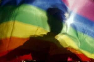 A gay man is silhouetted on a gay rainbow flag during a demonstration for gay rights in Hanoi, Vietnam, in November 2015.