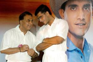 NEW DELHI, INDIA: Indian cricket team captain Sourav Ganguly (R) talks to former captain Sunil Gavaskar (L) as they stand beside a photograph of Ganguly during the unveiling of a cricket advertising campaign in New Delhi, 26 February 2004. LG Electronics India have unveiled LG