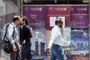 People walk past the Qatar Airways branch in the Saudi capital Riyadh, after it had suspended all flights to Saudi Arabia following a severing of relations between major Gulf states and gas-rich Qatar. Saudi Arabia was among the nations that closed its borders with Qatar, effectively blocking food and other supplies exported by land to Qatar.