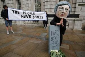 A demonstrator wears a mask depicting Britain