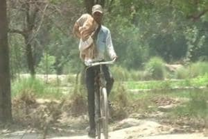Brij Mohan taking body of his niece Poonam back home from district hospital, Kaushambi on Monday