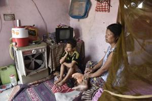 Joseph Khar, 32, with his wife Ngaideilum and child at their rented house in Bodella, West Delhi.