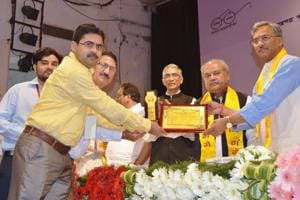 Chief minister Trivendra Singh Rawat felicitates Nainital DPRO Atul Pratap Singh for his contribution to make the state open defecation free, in Dehradun on Thursday.