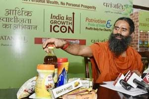 """Ramdev shows """"Patanjali"""" products before addressing a press conference in New Delhi."""