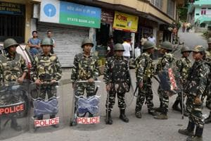 Security personnel stand guard on a streets in front of a shuttered ATM machine during an indefinite strike of government offices and banks called by the Gorkha Janmukti Morcha (GJM) party in Darjeeling on June 14, 2017.