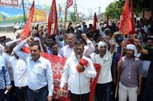 Hero Cycles employees along with workers unions protest outside Hero Cycle office at NH-1 in Ludhiana on Friday.