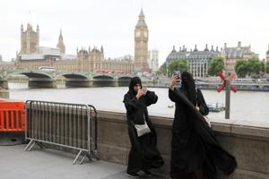Two women wearing burqas clicking photographs opposite the Houses of Parliament, London, Britain, June 7, 2017