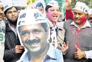 Aam Aadmi Party supporters hold up a placard of party national convener and Delhi CM Arvind Kejriwal.