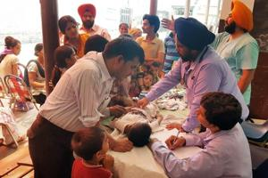 Doctors examining patients at a medical camp in Makkar Colony in Ludhiana on Sunday.
