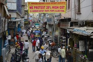 Pedestrians walk below a banner calling for a protest against the steep hike in the proposed new goods and services tax (GST) regime for sanitary and hardware products in Bangalore on June 29, 2017.
