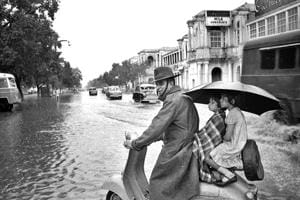 Afamily soaks in the rain at Minto Bridge. Monsoon used to be the time for picnics, family and cultural gatherings and feast for Delhiites.