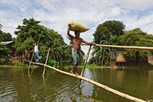 Villagers use a makeshift bamboo bridge to move across a flooded area in Morigaon district of Assam.