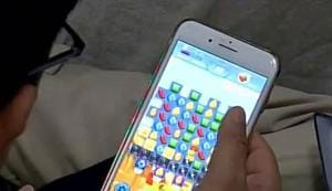 A police officer playing the Candy Crush Saga game on his mobile phone.