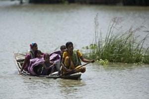 An woman with her family and her belongings paddles a boat through flood waters at Khola Bhuyan village, east of Guwahati, Assam, July 5, 2017.