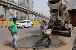 Construction workers mend the potholed stretch of Golf Course Road on Wednesday.