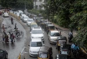 A long line of vehicles wait on a road leading to the Khar subway.