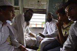Junaid's  two brothers (first and second from right) travel on an EMU train at Ballabhgarh railway station in Haryana
