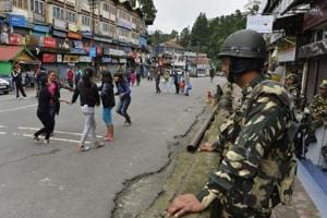 Girls play as paramilitary troops stand guard at Chowkbazar area during an indefinite strike called by Gorkha Janamukti Morcha (GJM) in Darjeeling.
