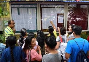 Students and parents look at the first lists put up outside HR College in Mumbai on Tuesday.